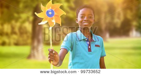 Happy boy in the park with pinwheel against trees and meadow