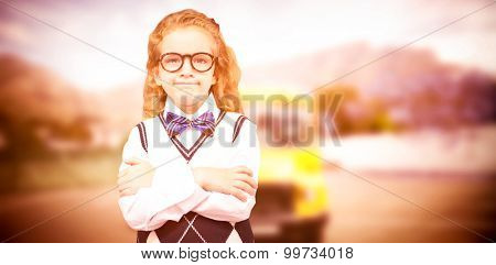 Cute pupil with arms crossed against yellow school bus waiting for pupils