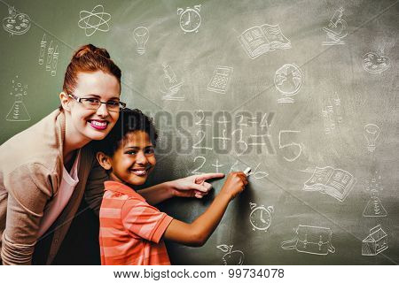 School doodles against teacher assisting boy to write on blackboard in classroom