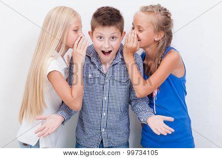 Teenage girsl whispering in the ears of a secret teen boy on white  background