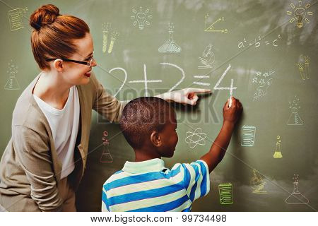 School subjects doodles against teacher assisting boy to write on blackboard in classroom