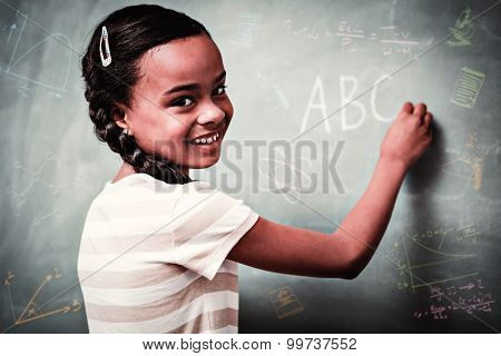 Math and science doodles against cute little girl writing abc on blackboard