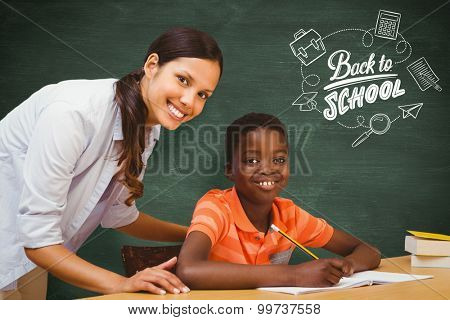 Teacher assisting boy with homework in library against green chalkboard