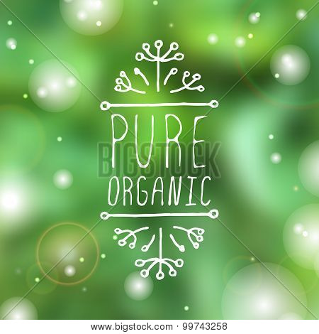 Pure organic - product label on blurred background.