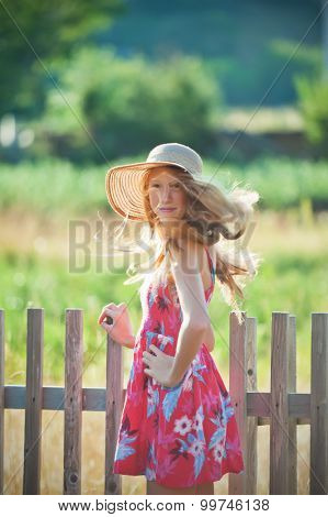 Young redhead girl in country style outfit, standing over wooden fence