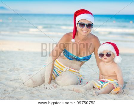 Baby and mother on the beach. Christmas concept