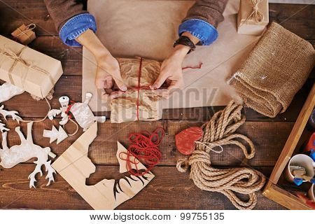 Hands of young man tying up wrapped xmas gift with red thread