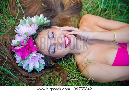 Sensual lady in wreath and perfect smile on grass