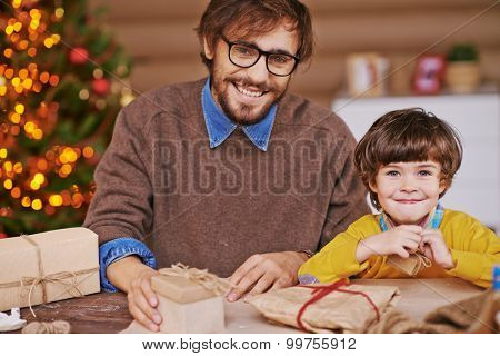 Happy young man and his son looking at camera with packed xmas gifts near by