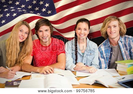 College students doing homework in library against composite image of digitally generated united states national flag
