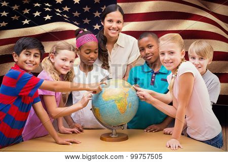 Cute pupils and teacher looking at globe in library against composite image of digitally generated united states national flag