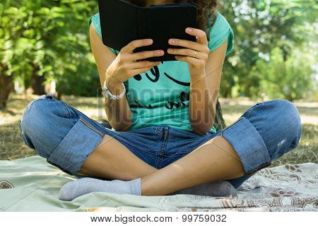 The Girl Reads The E-book In A Meadow
