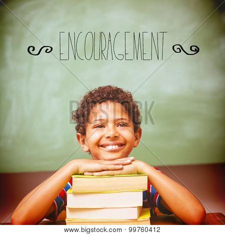 The word encouragement against little boy with stack of books in classroom