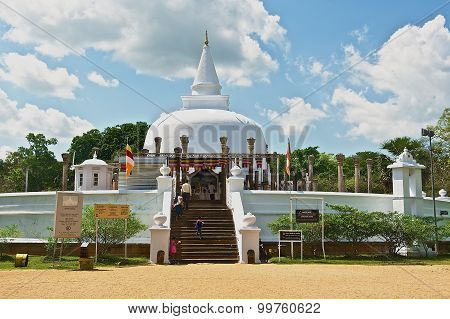People go to Lankarama stupa in Anuradhapura, Sri Lanka.