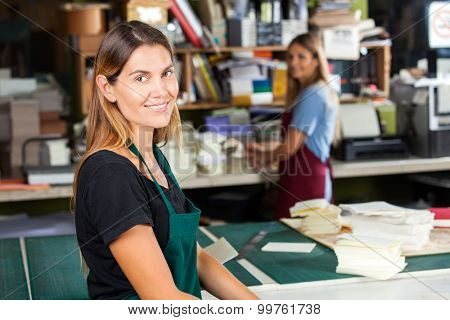 Portrait of smiling mid adult female worker standing in paper factory