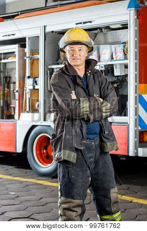 Portrait of confident fireman standing arms crossed against truck at fire station