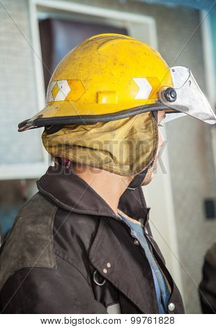Side view of male firefighter wearing yellow helmet at fire station