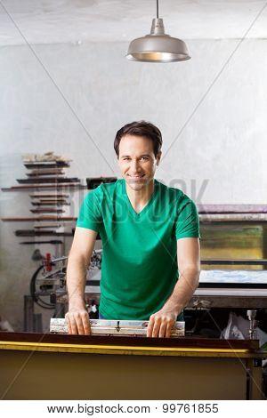 Artist making silkscreen print in studio