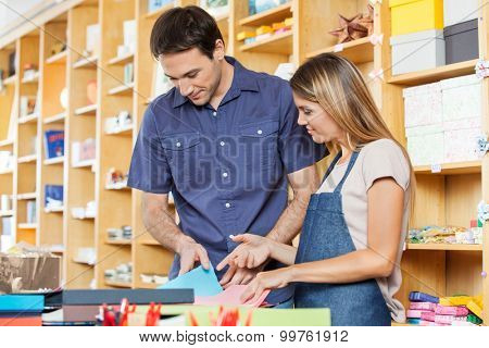 Mid adult saleswoman assisting male customer in choosing greeting card at shop