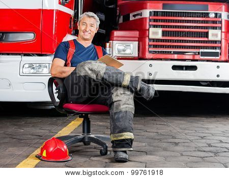 Full length portrait of happy firefighter sitting on chair against trucks at fire station