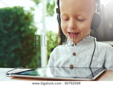 Adorable Little Boy Listening To Recorded Music
