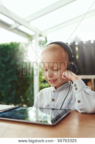 Little Boy Smiling In Delight Listening To Music