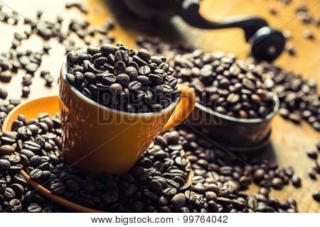 Coffee. Coffee cup full of coffee beans, coffee grinder in the background.
