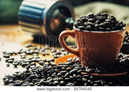 Coffee. Coffee cup full of coffee beans, coffee grinder in the background