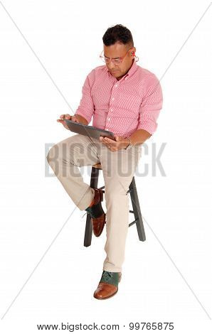 Hispanic Man Sitting With Tablet Pc.