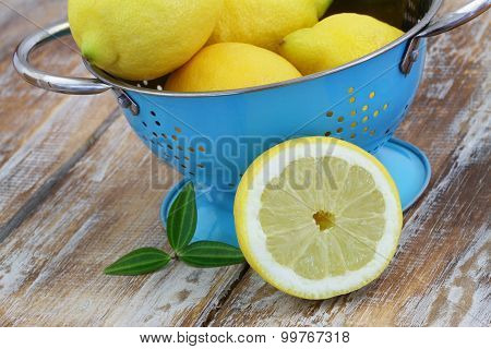 Lemon leaning against blue colander on rustic wooden surface