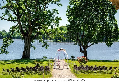 Lakeside Wedding Ceremony. Wedding Chairs And Wedding Arch On A Lawn