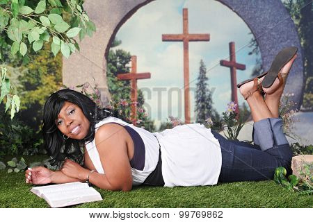 An attractive African American woman laying on the springtime grass as she reads her Bible.  Sky, trees and three crosses are visible through the hole in a giant donut shaped rock behind her.