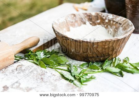 wooden bowl with flour for dough with wooden board and rolling-pin