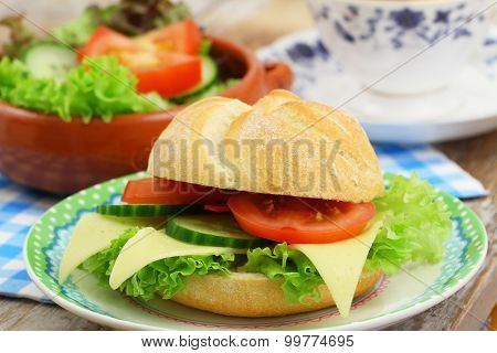 Bread roll with cheese, lettuce, tomato and cucumber, closeup