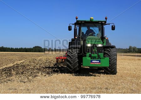 John Deere 8370R Tractor On Field With Headlights On