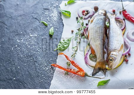 Fresh fish ide on a black stone slab surrounded by herbs, slices of lemon, peppers peas and salt.