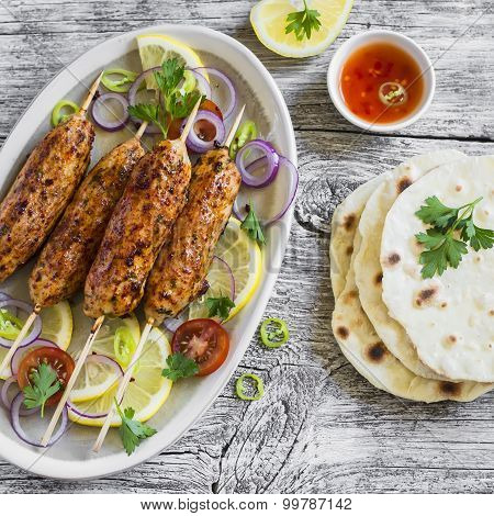 Chicken Kebabs On Wooden Skewers On An Oval Plate And Homemade Tortilla On A Light Wooden Surface