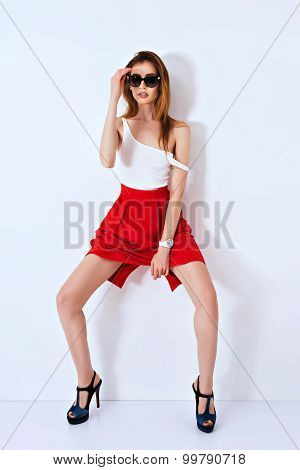 Vogue fashion model woman posing in red mini skirt on white studio background.