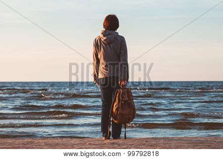 Young Tourist Woman With Backpack  Looking To Sea At Sunset.