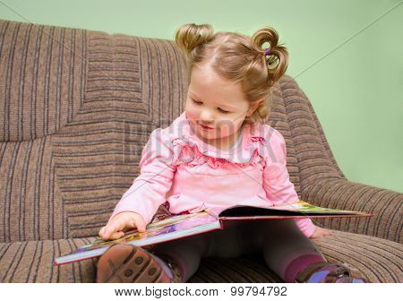 Pretty Little Girl Sitting On A Sofa And Looking At A Children's Picture Book.