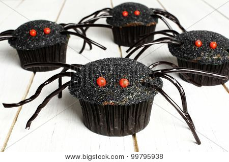 Halloween spider cupcakes on white wood