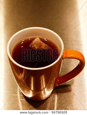 Tea Bag Steeping In Orange Ceramic Cup