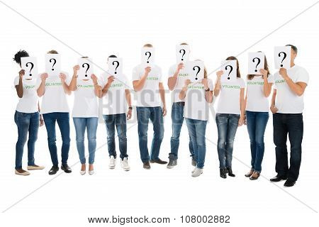 Volunteers Covering Faces With Question Mark Signs