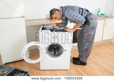 Handyman Checking Washing Machine With Flashlight