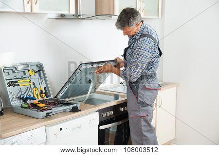 Repairman Examining Stove In Kitchen