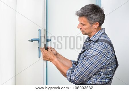 Carpenter Fixing Lock In Door With Screwdriver