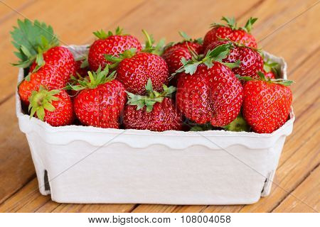 A pulp package made of recycled paper filled with huge Strawberries on a wooden table