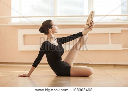 Young ballet dancer performing exercise while sitting on floor