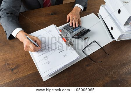 Businessman Checking Receipts At Desk