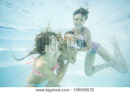 Happy family swimming underwater.